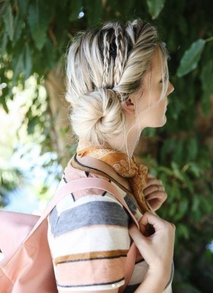 side view of woman with blonde hair in twisted headband side bun with multi braids wearing stripe top and backpack