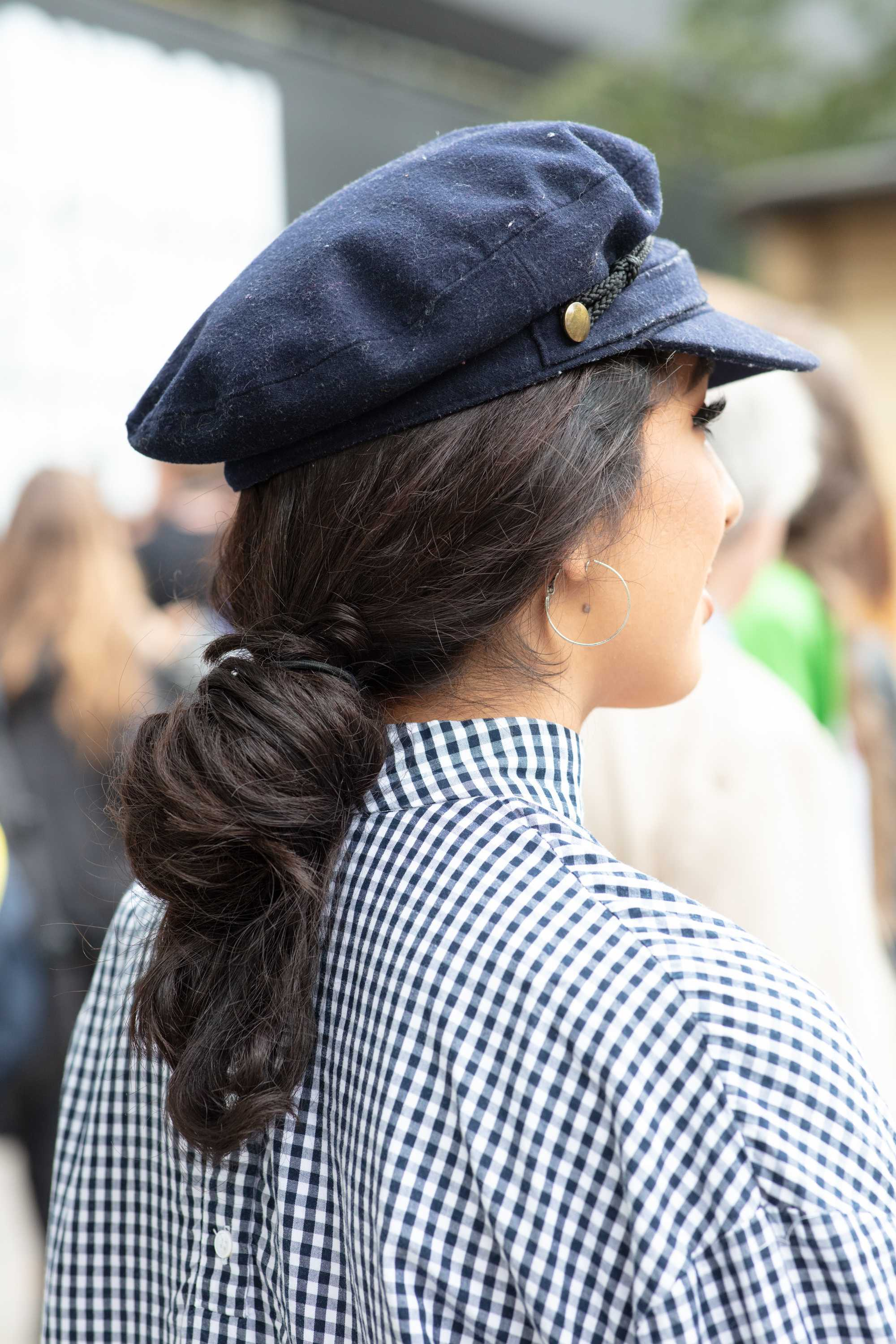 London Fashion Week street style hair: Close up shot of woman with long dark brown hair styled into a loose bun/ponytail hairstyle, wearing a baker boy hat and a checked shirt, while posing on the street