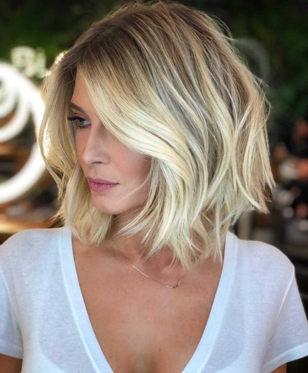 Woman with bright blonde short bob with wavy bangs