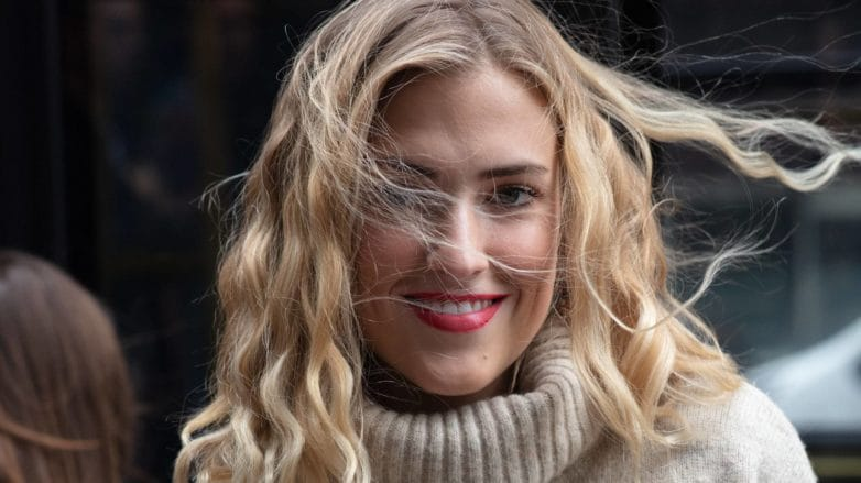Hair hacks for winter: Shot of a woman with beige turtleneck, with medium golden blonde curly hair posing for street style picture