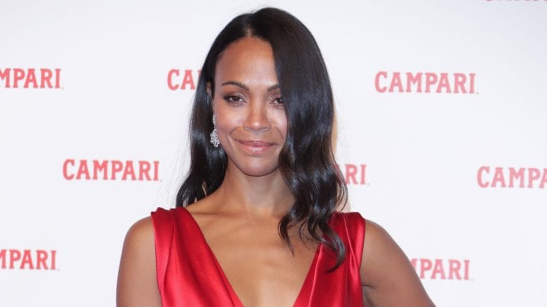 actress zoe saldana on the red carpet in a red v neck silk dress with silky shiny curled hair