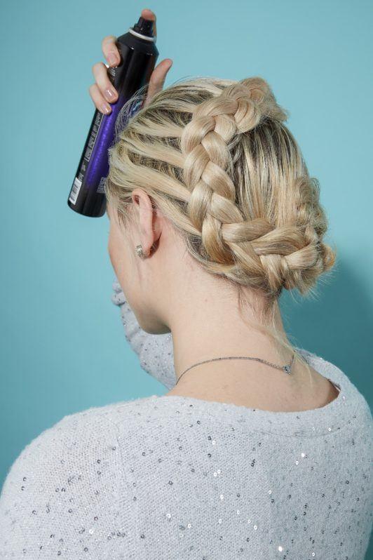 Blonde woman using hair spray on flower braid