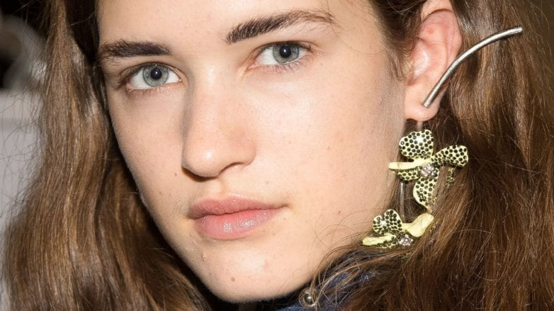 Hair thickening shampoo: Close-up of a brunette model with thick medium length hair tucked behind her ears, backstage at acne FW18 runway show