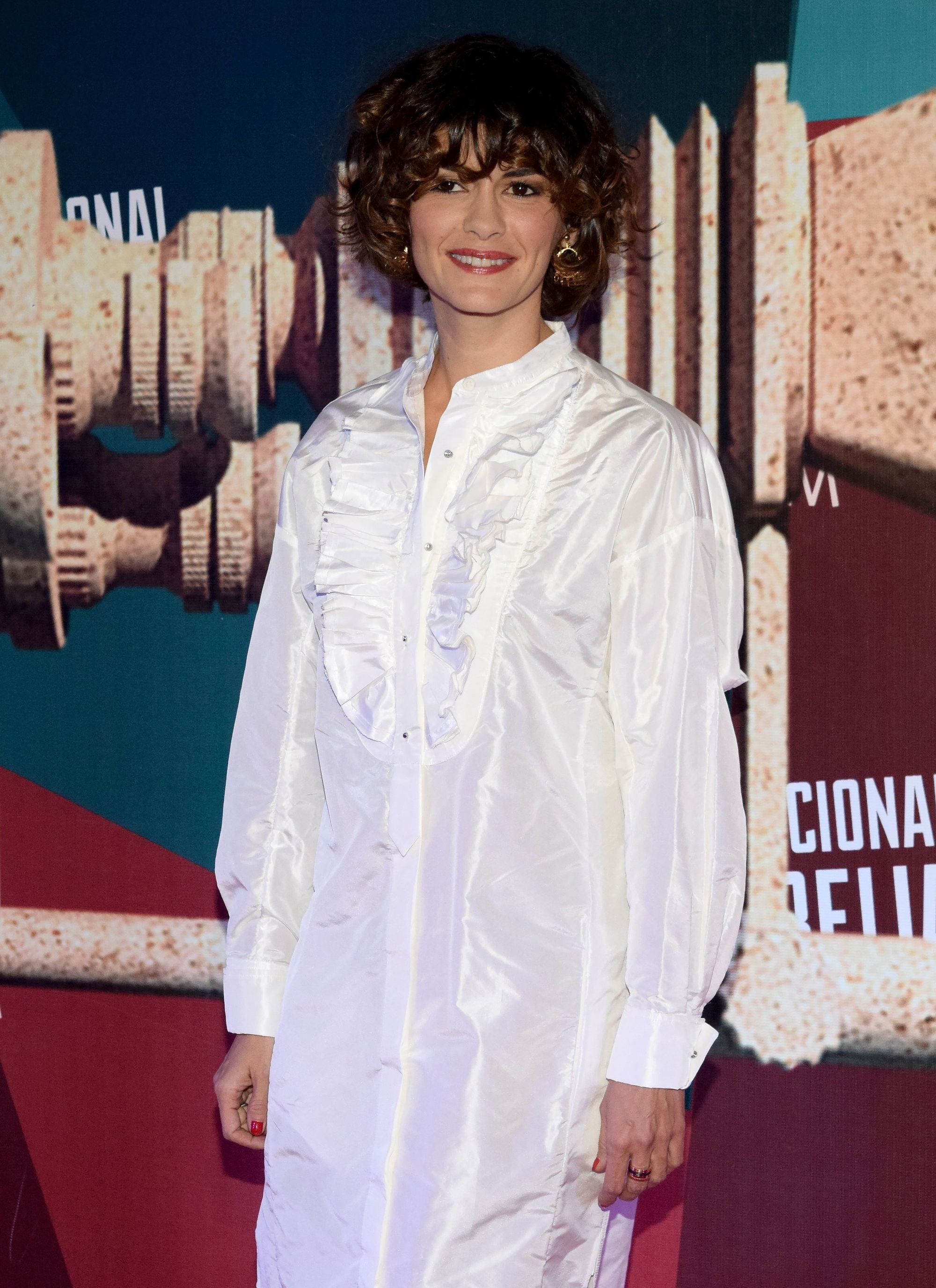 audrey tautou popular short shag hairstyle on curly brown bob-length hair wearing white oversized shirt dress