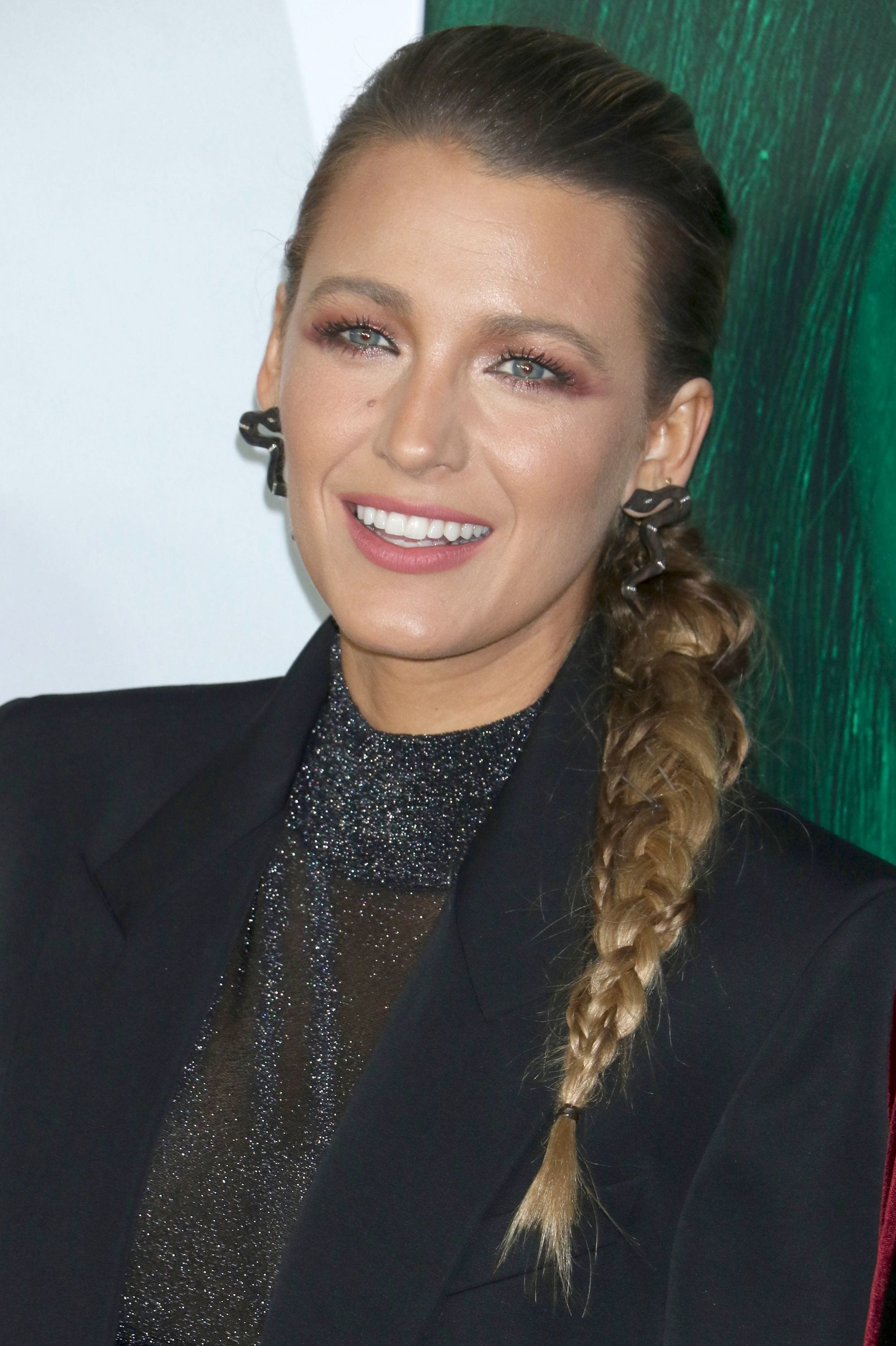 Side braid hairstyles: Blake Lively with long blonde side ponytail braid wearing a black outfit.