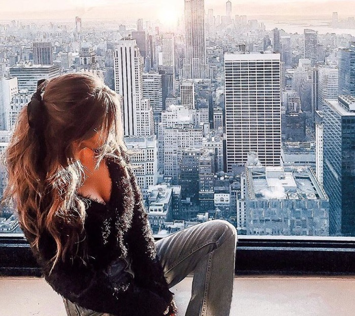 close up shot of woman with half up half down hairstyle, wearing jacket and grey jeans, posing next to a window over looking new york city