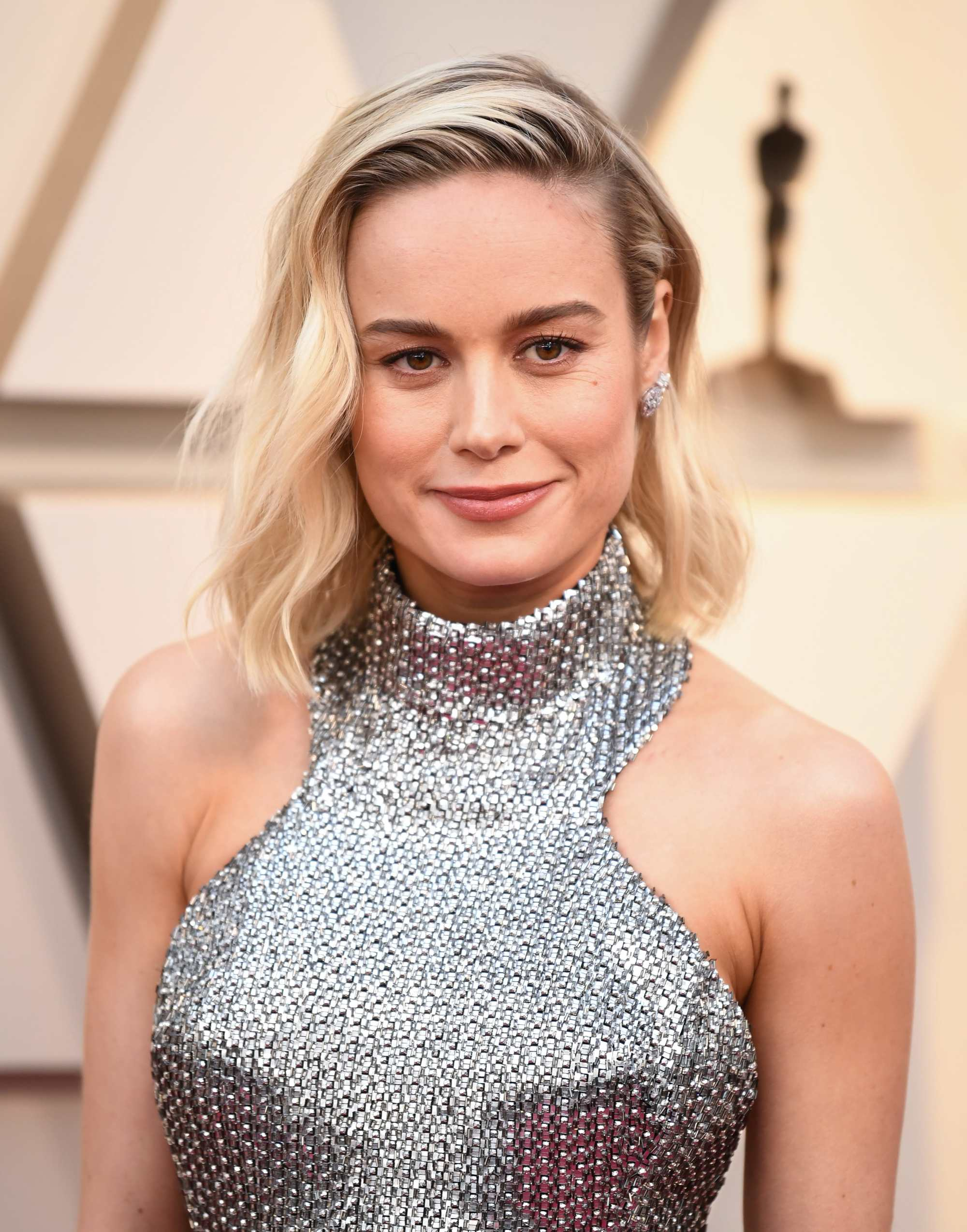 Oscars 2019 hairstyles: Brie Larson at the 2019 Oscars with platinum blonde hair styled in a side-parted tousled wavy lob, wearing a halterneck sparkly silver dress