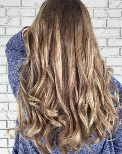 back view of a woman with blondey brown curled hair with highlights and lowlights