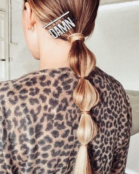 Second day hair: Woman with long golden blonde straight hair in low bubble ponytail with jewelled hair clip.