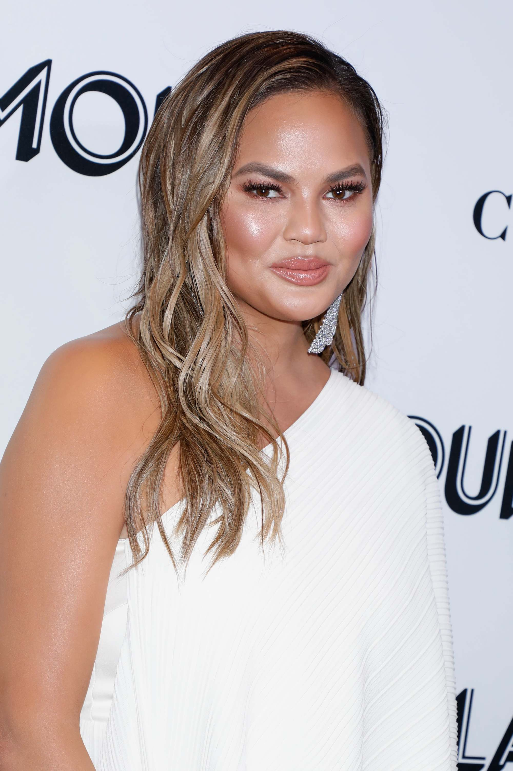 Highlights and lowlights: Chrissy Teigen with wavy medium length highlighted brown hair wearing a white one-shoulder dress.