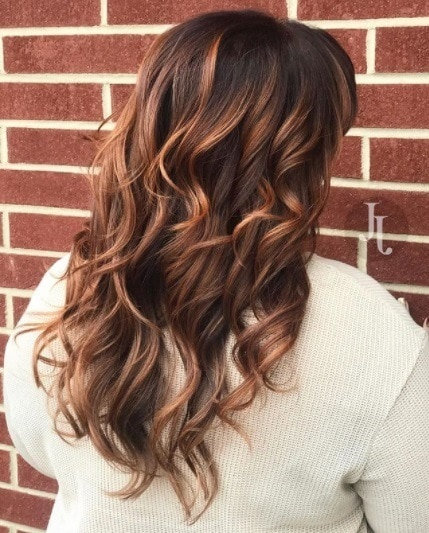 back view of a woman with curled copper highlighted hair