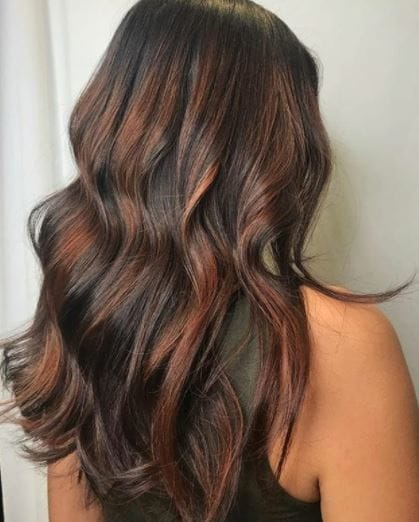 Copper highlights: back view of woman with long wavy brown hair with copper highlights wearing black vest