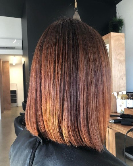 Copper highlights: Side profile of a woman with a copper coloured blunt long bob