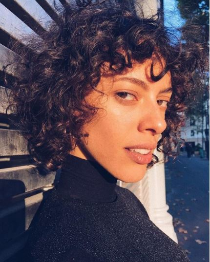 Woman with short brown curly hair with a fringe