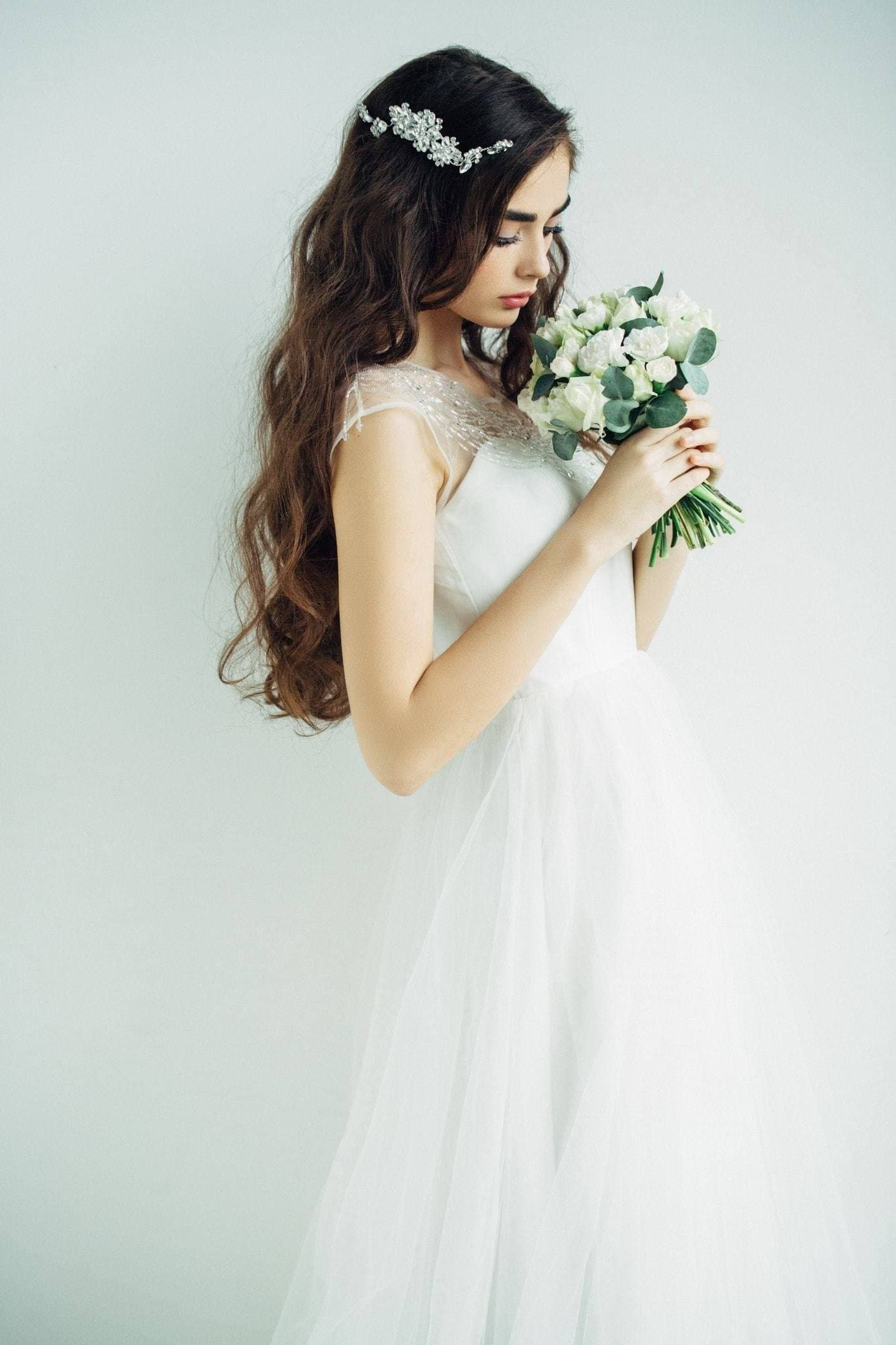 Curly wedding hair: Brunette bride with long curly hair with a diamante barette hair clip