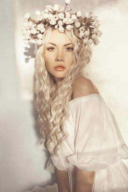 Curly wedding hair: Photo of a woman with long platinum silver blonde wavy hair with an elaborate white flower crown
