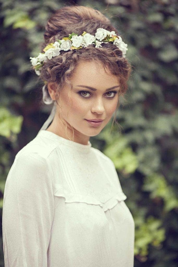 Curly wedding hair: Photo of a woman with light brown naturally curly hair in a high bun with a flower crown