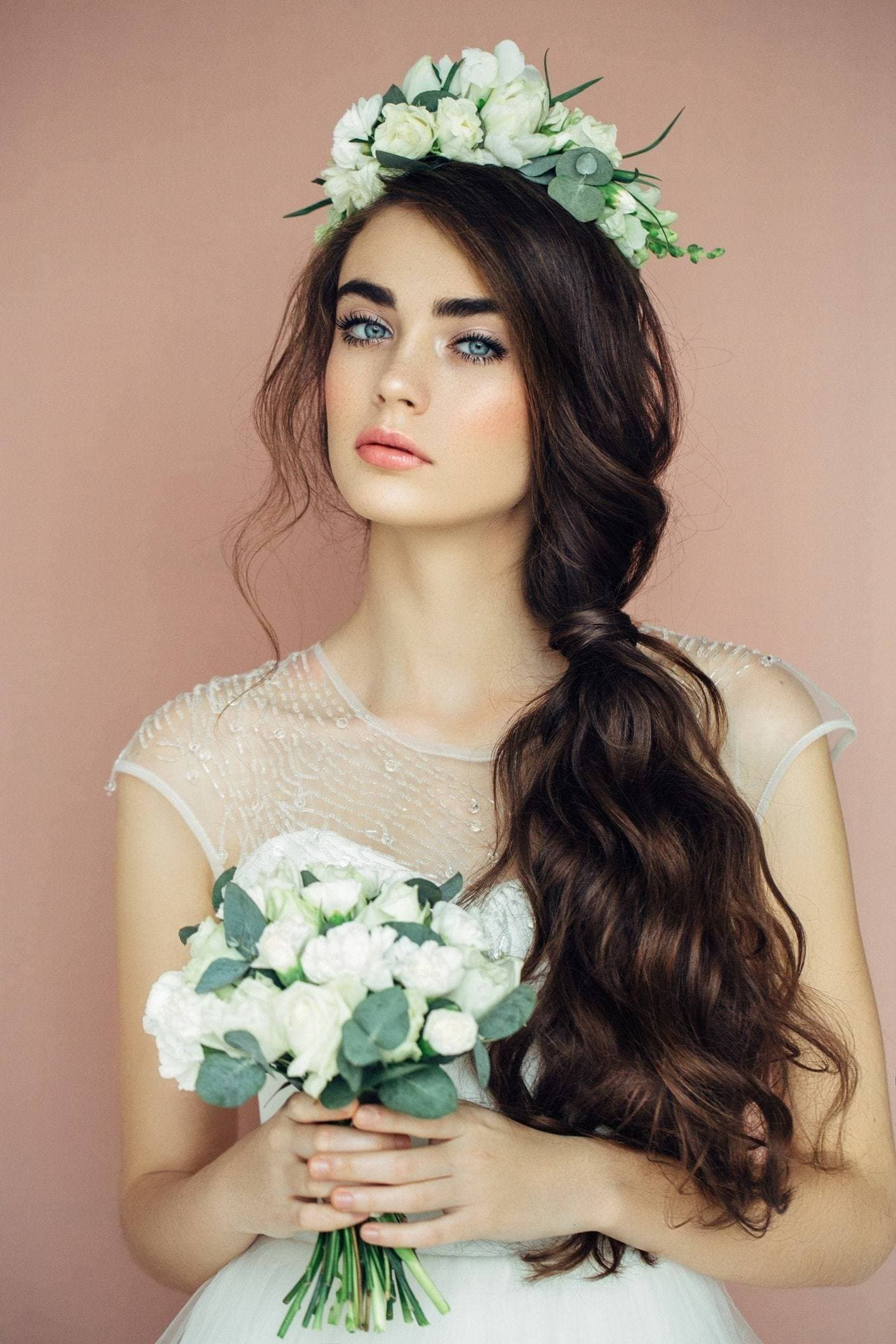 Curly wedding hair: Brunette bride with long curly hair in a low side ponytail with a flower crown