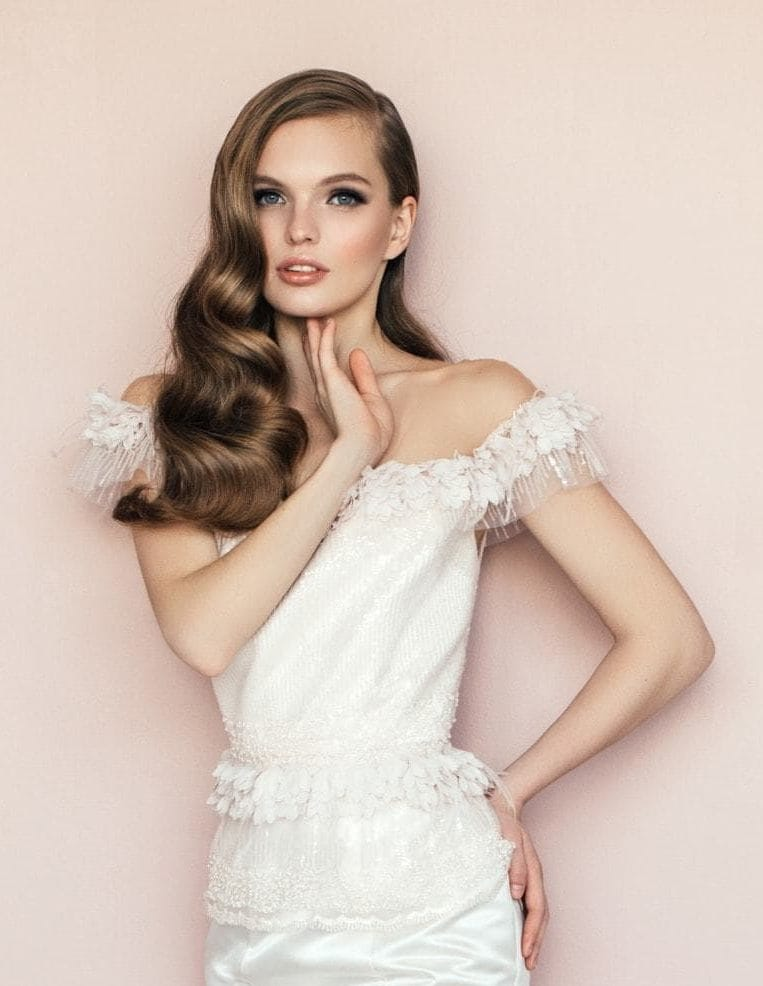 Curly wedding hair: Photo of a brunette bride with side-swept Hollywood waves