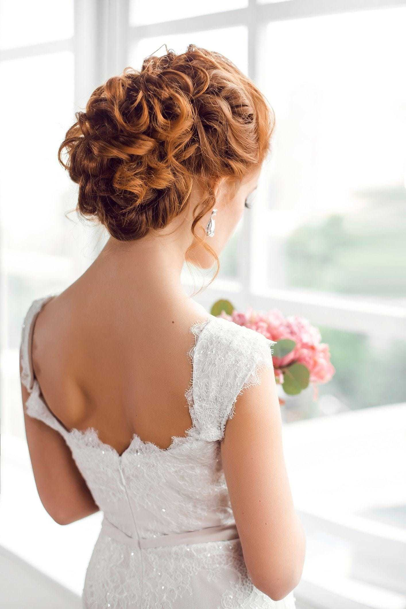 Curly wedding hair: Back view of a redhead bride with her hair in a curly pinned updo