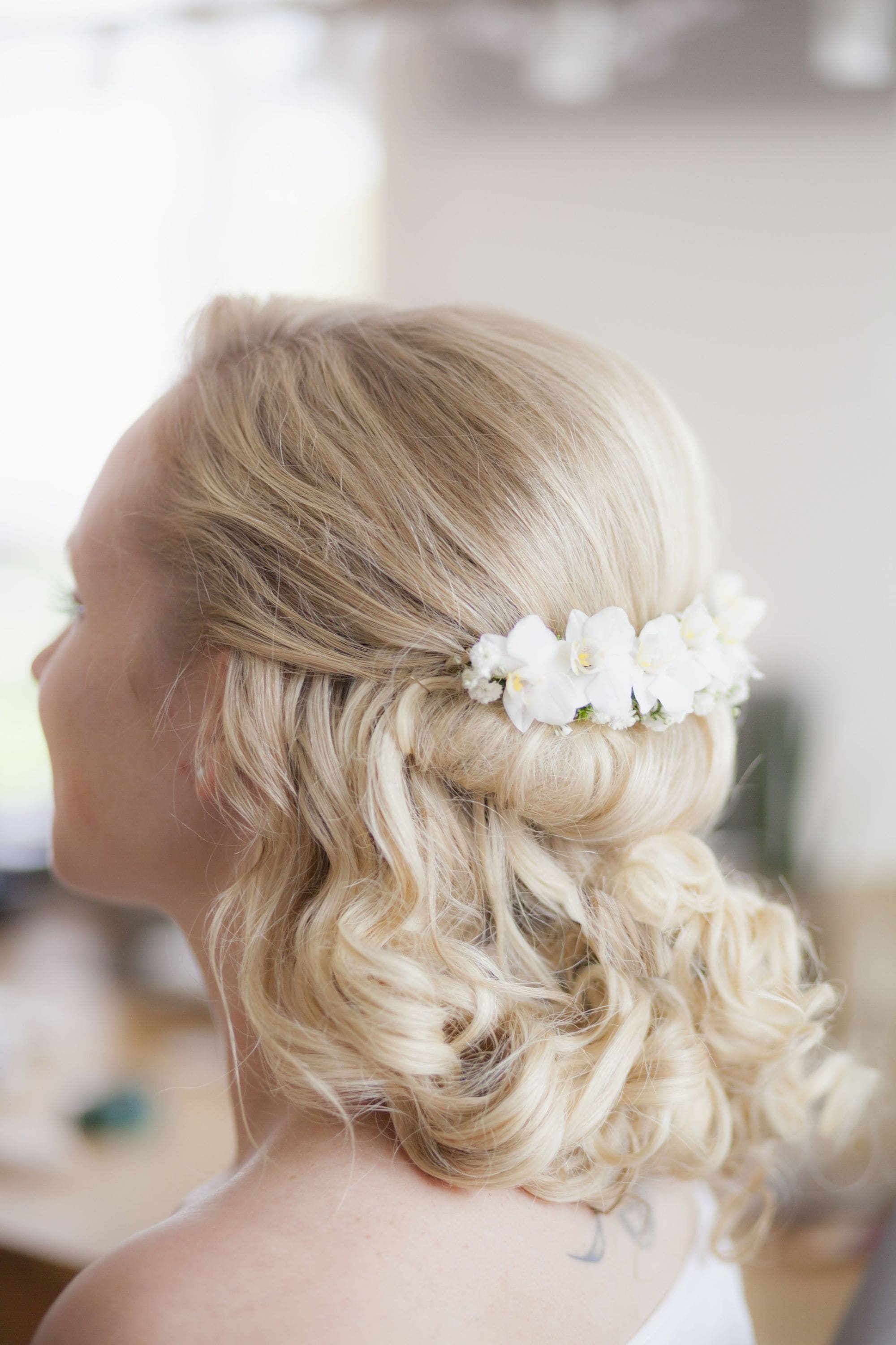 Curly wedding hair: Back view of a blonde bride with mid-length curled hair in a rolled half-updo with white flower accessories