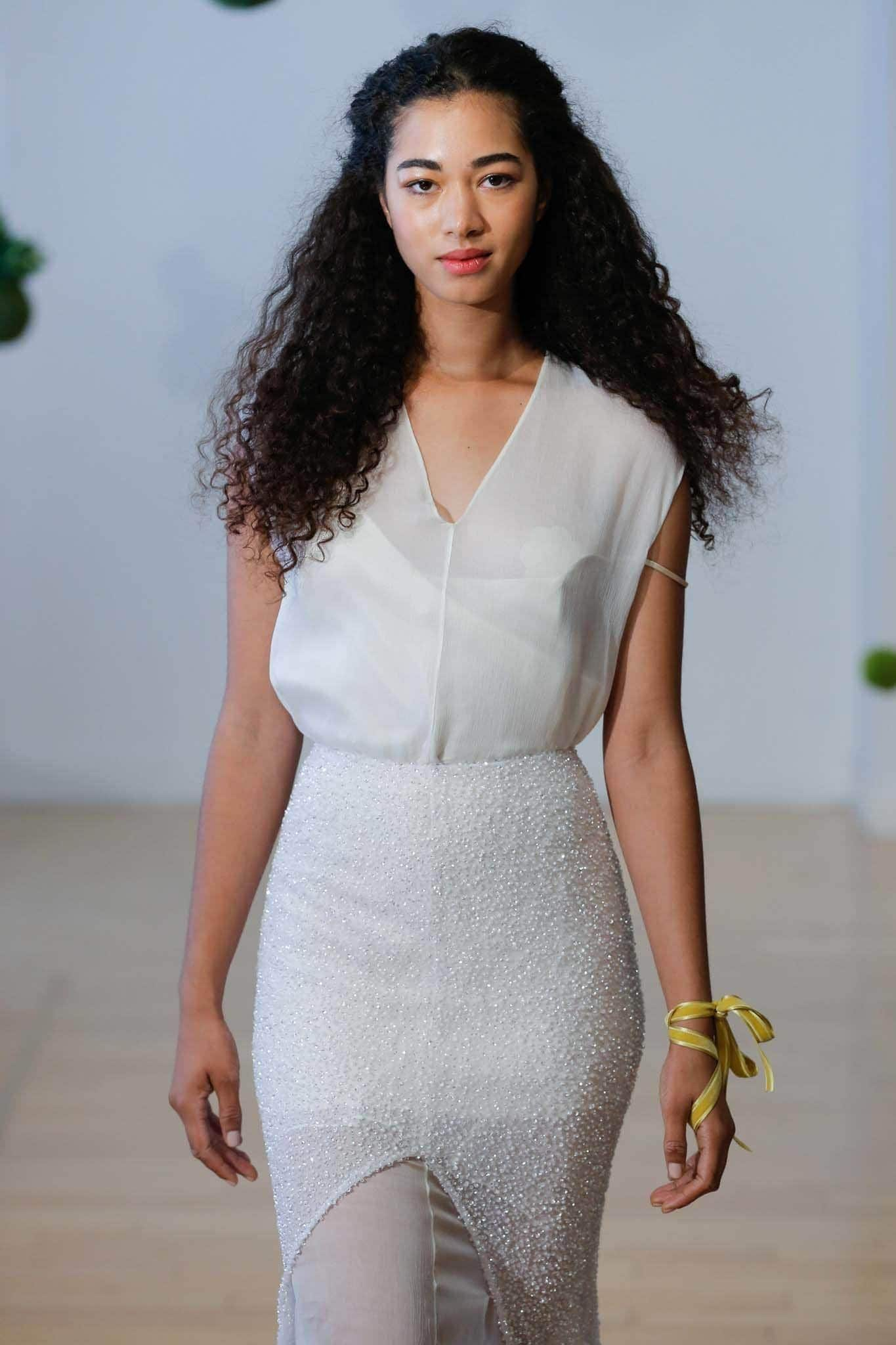 Curly wedding hair: Bridal runway model with long dark natural curly hair with a twisted half-up