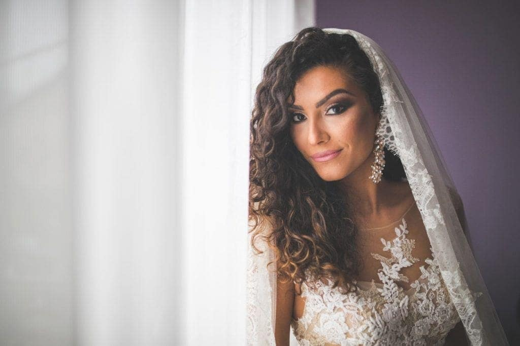 Curly wedding hair: Photo of a bride with long curly brunette ombre hair, wearing a veil