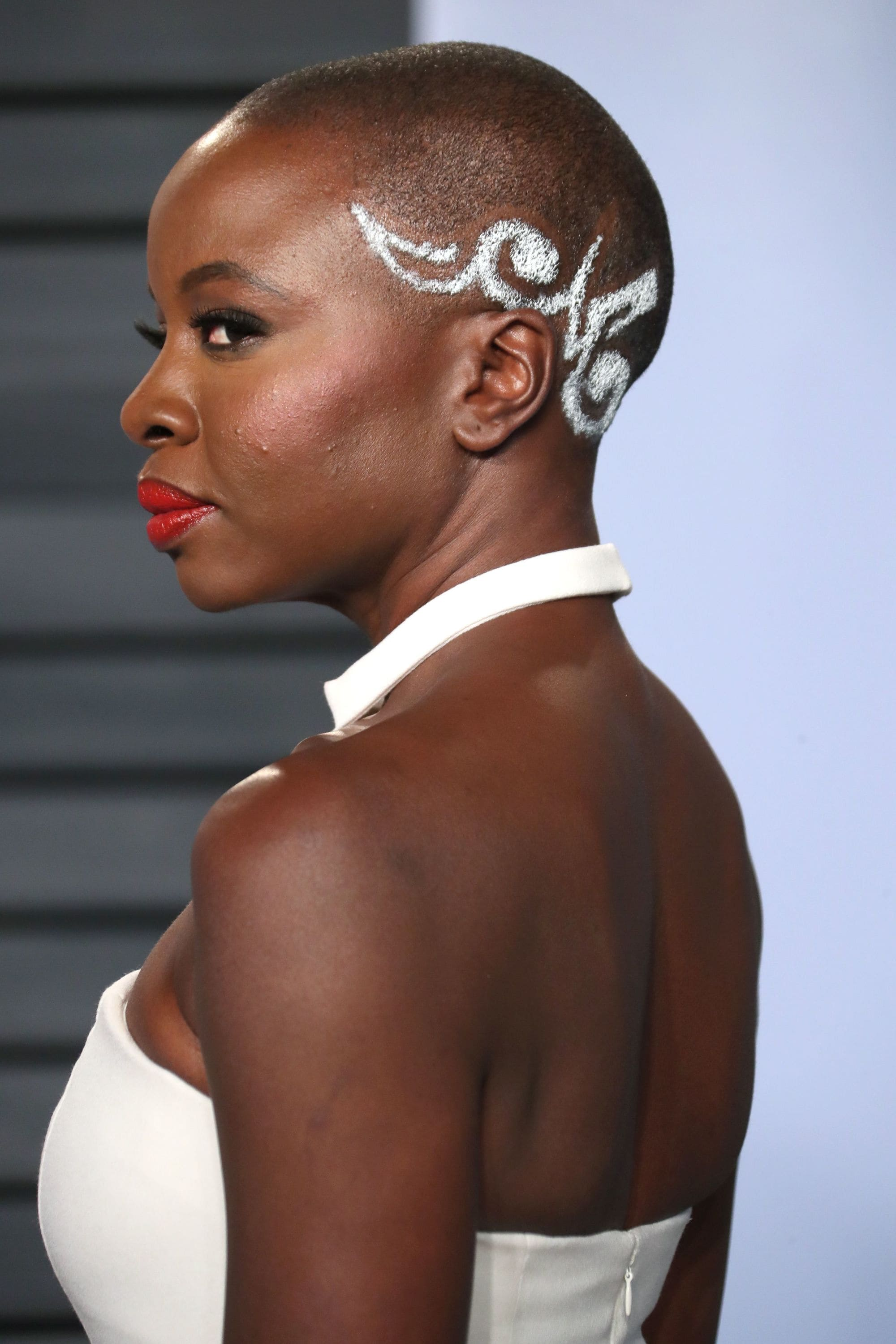 danai gurira shaved buzzcut with white pattern design on the side at movie awards wearing white dress