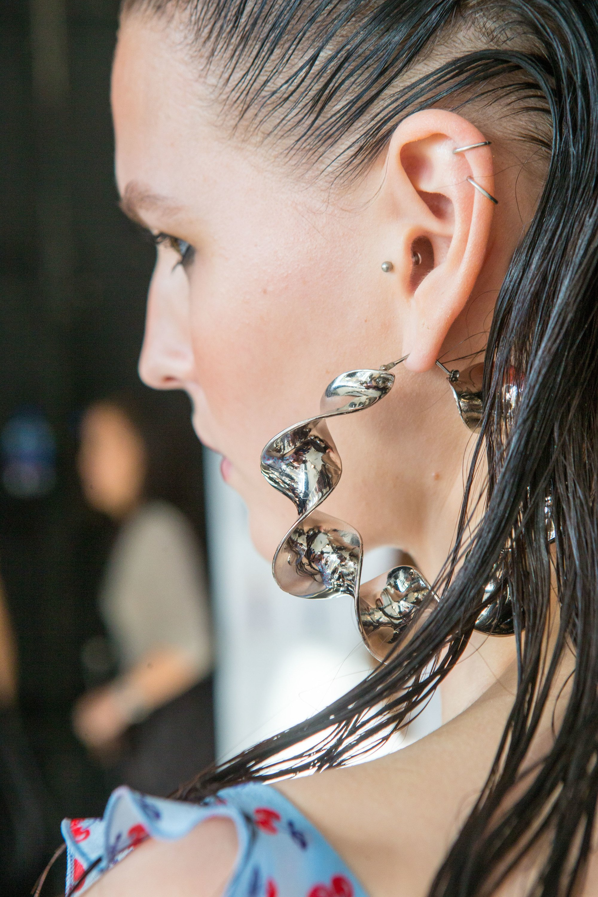 close up of model backstage at runway show with wet look brown straight hair