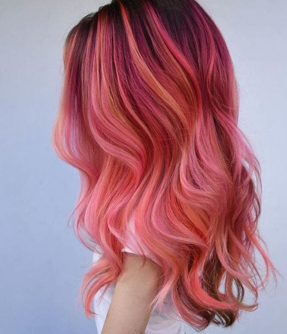 flamingo hair: side view of woman with long pink multi-toned wavy long hair