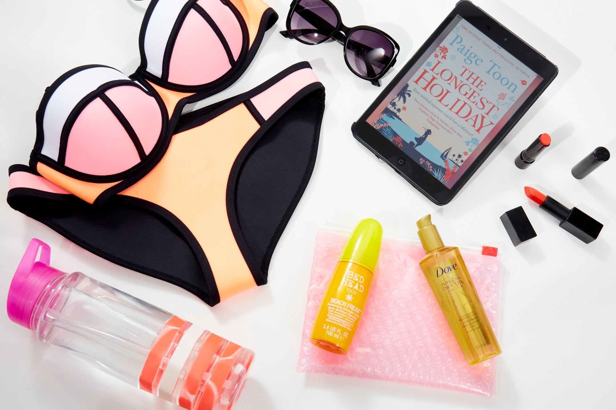 flatlay of beach products for all things hair holiday essentials