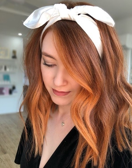 Copper highlights: Woman with mid-length curled copper hair with face-framing highlights