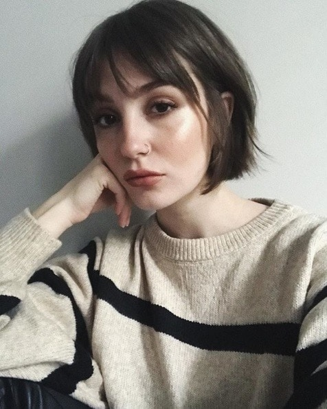 Woman with a brunette French girl inspired bob with bangs
