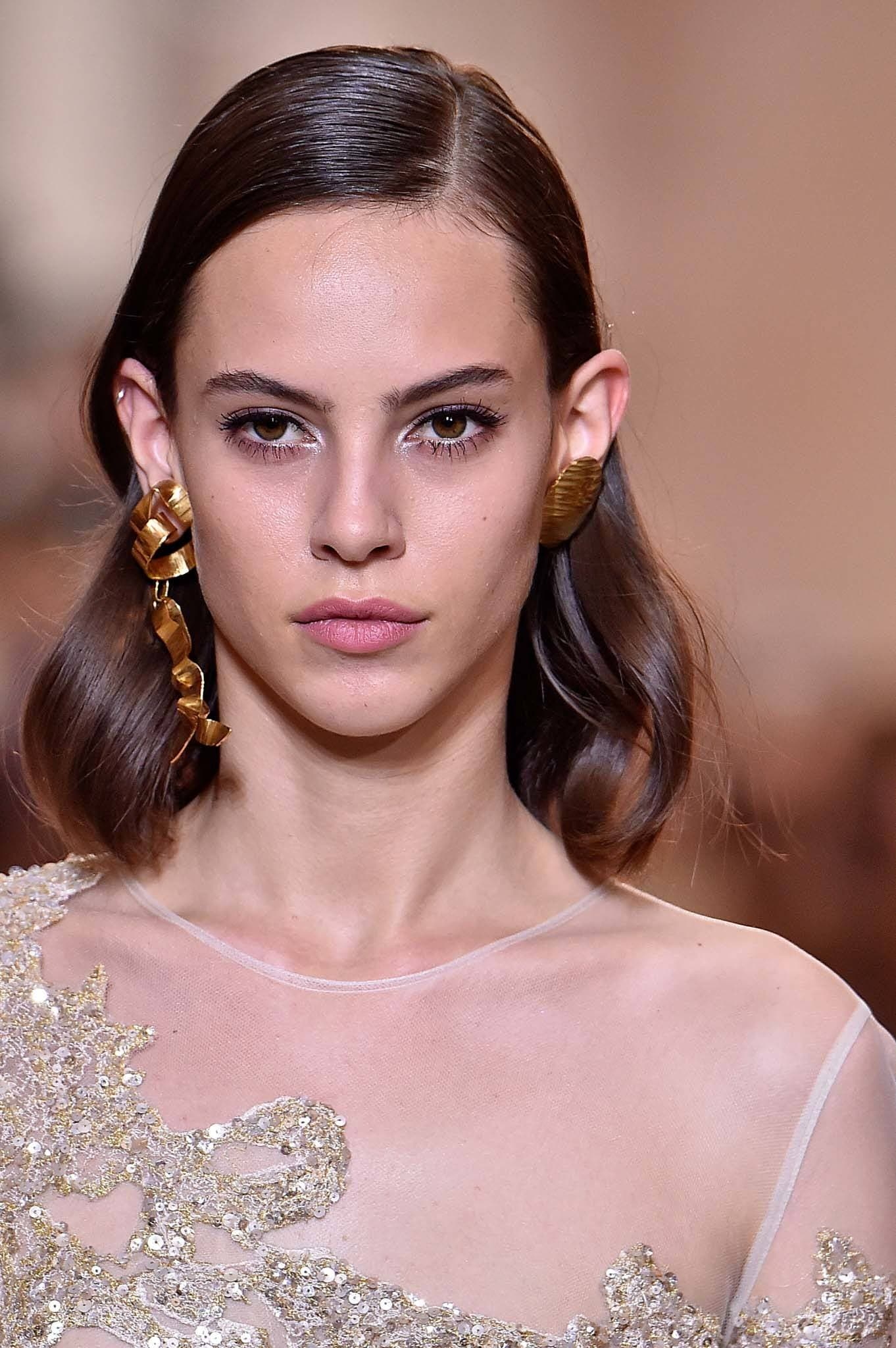 Wedding guest hair: Shot of a model with medium brown glossy waves on the runway, wearing a white dress with earrings on the runway