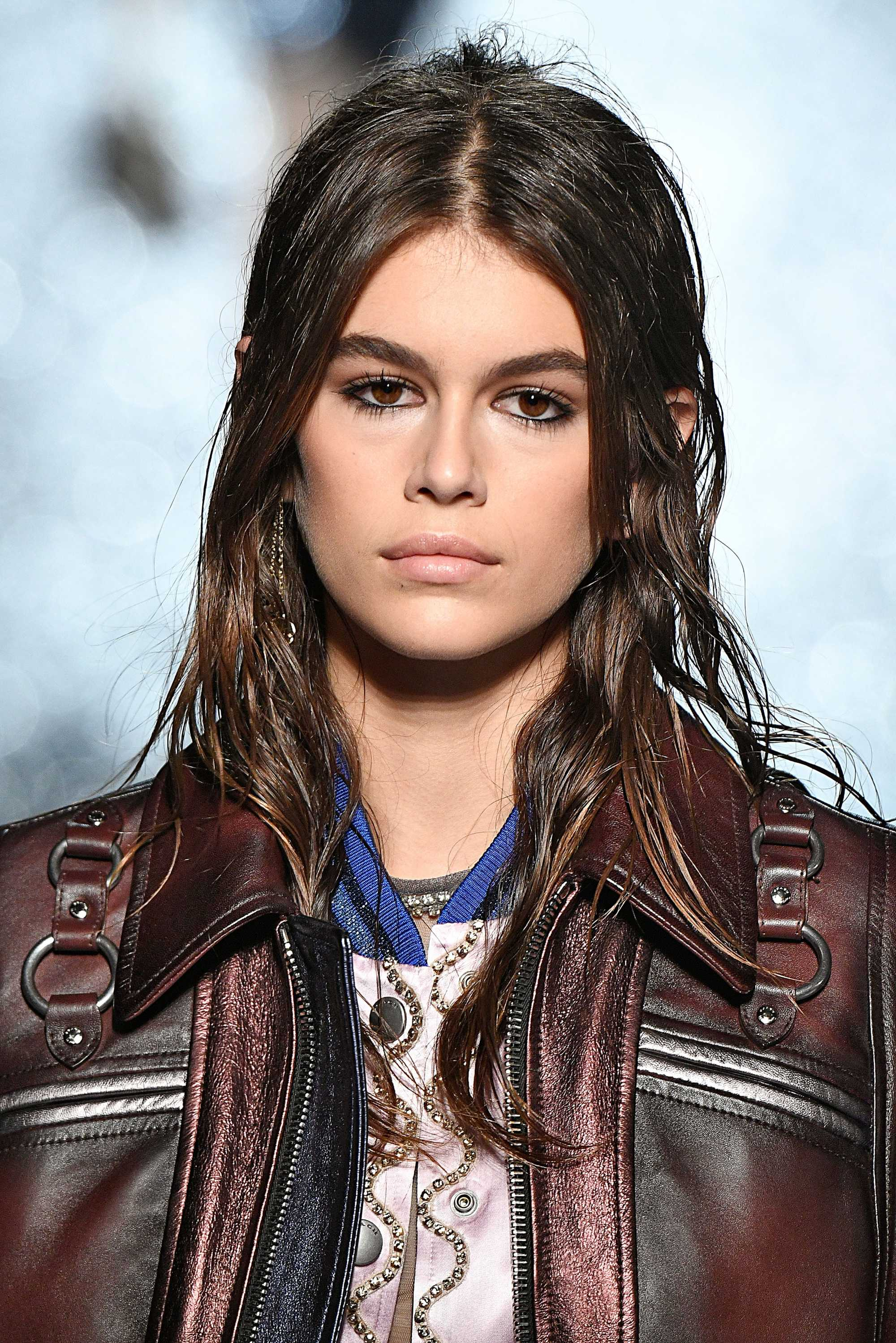 kaia gerber on coach ss18 runway with brown wet look hair in half-up, half-down wavy style