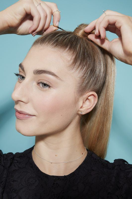 Blonde woman creating high ponytail hairstyle