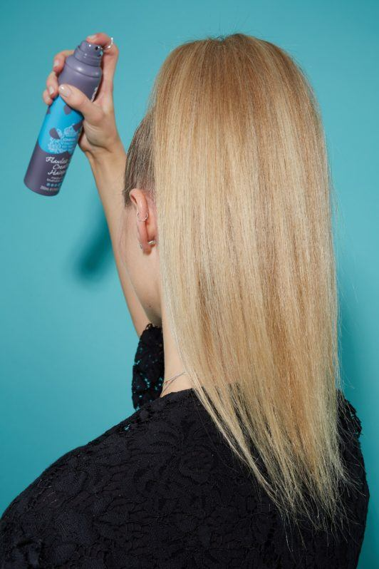 Blonde woman with high ponytail spraying hairspray