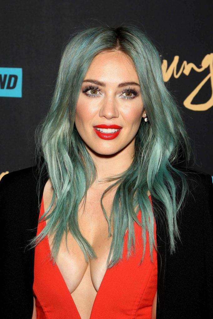 Green hair; Lizzie Mcguire actress Hilary Duff with green dyed long hair softly curled wearing a red plunging dress with a black jacket
