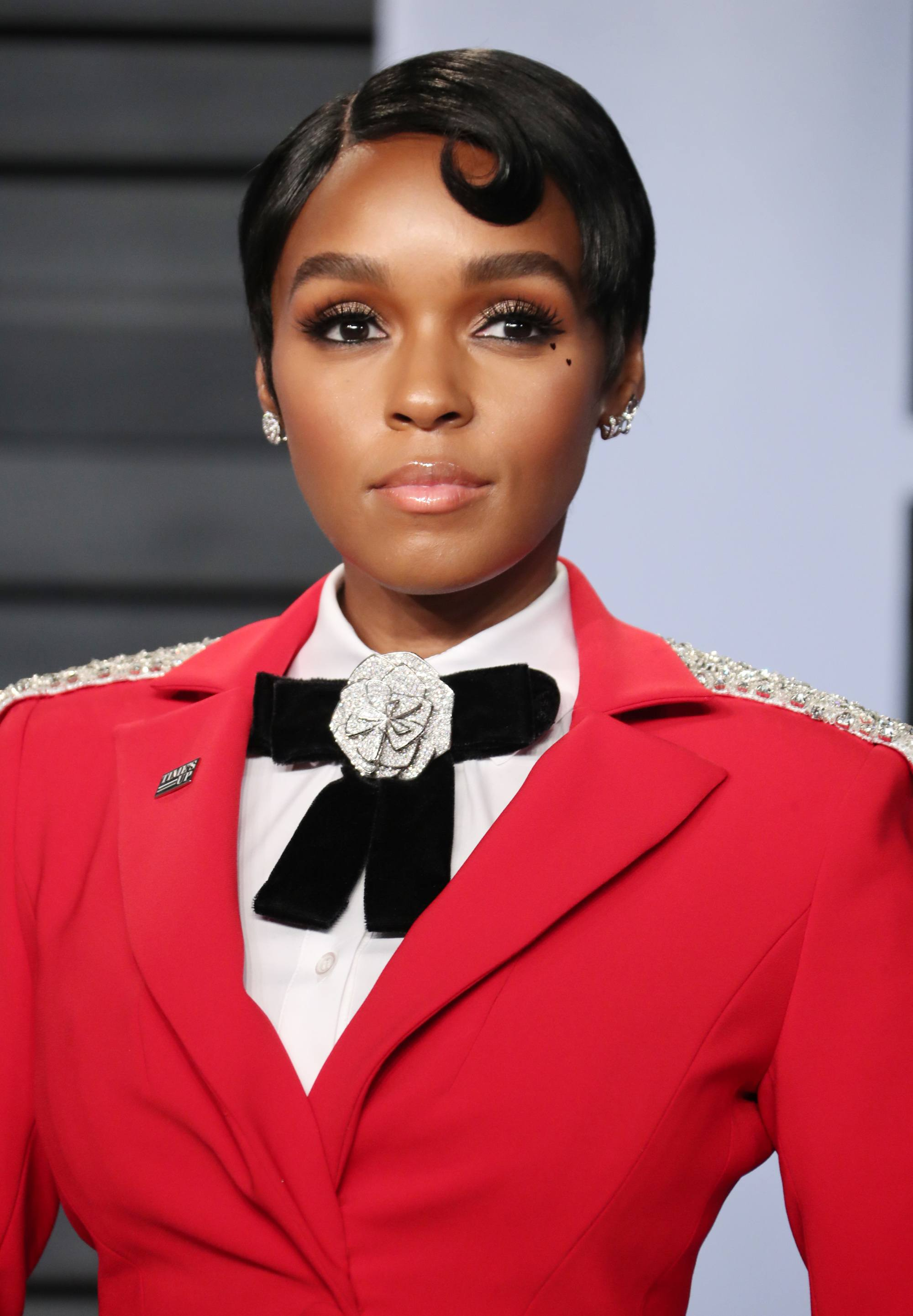 janelle monae with short dark brown pixie hair with retro wave finish wearing red blazer, white shirt and black big bow tie