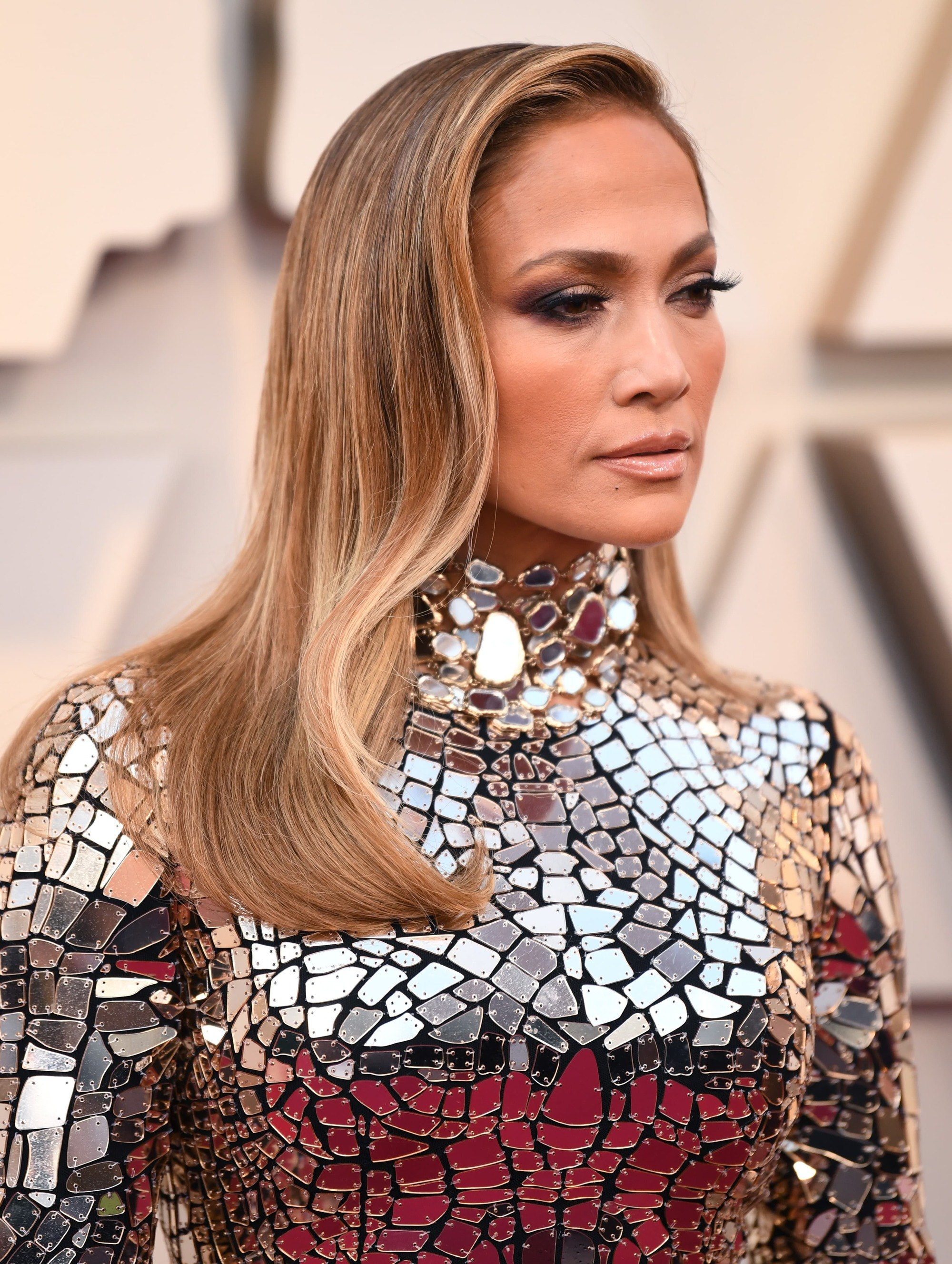 Oscars 2019 hairstyles: Jennifer Lopez (J Lo) at the 2019 Oscars with side-swept wavy mid-length bronde hair, wearing a high neck sequin dress