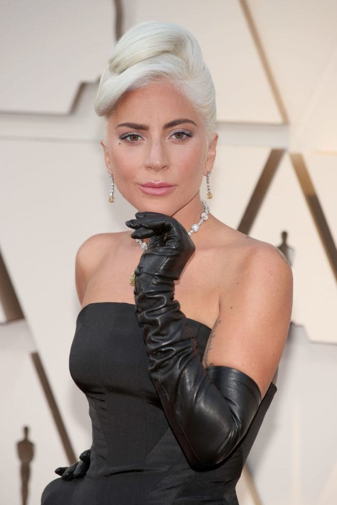 Oscars 2019 hairstyles: Lady Gaga at the 2019 Oscars with her platinum blonde hair in an Audrey Hepburn inspired chignon updo, wearing a black strapless dress and long black gloves