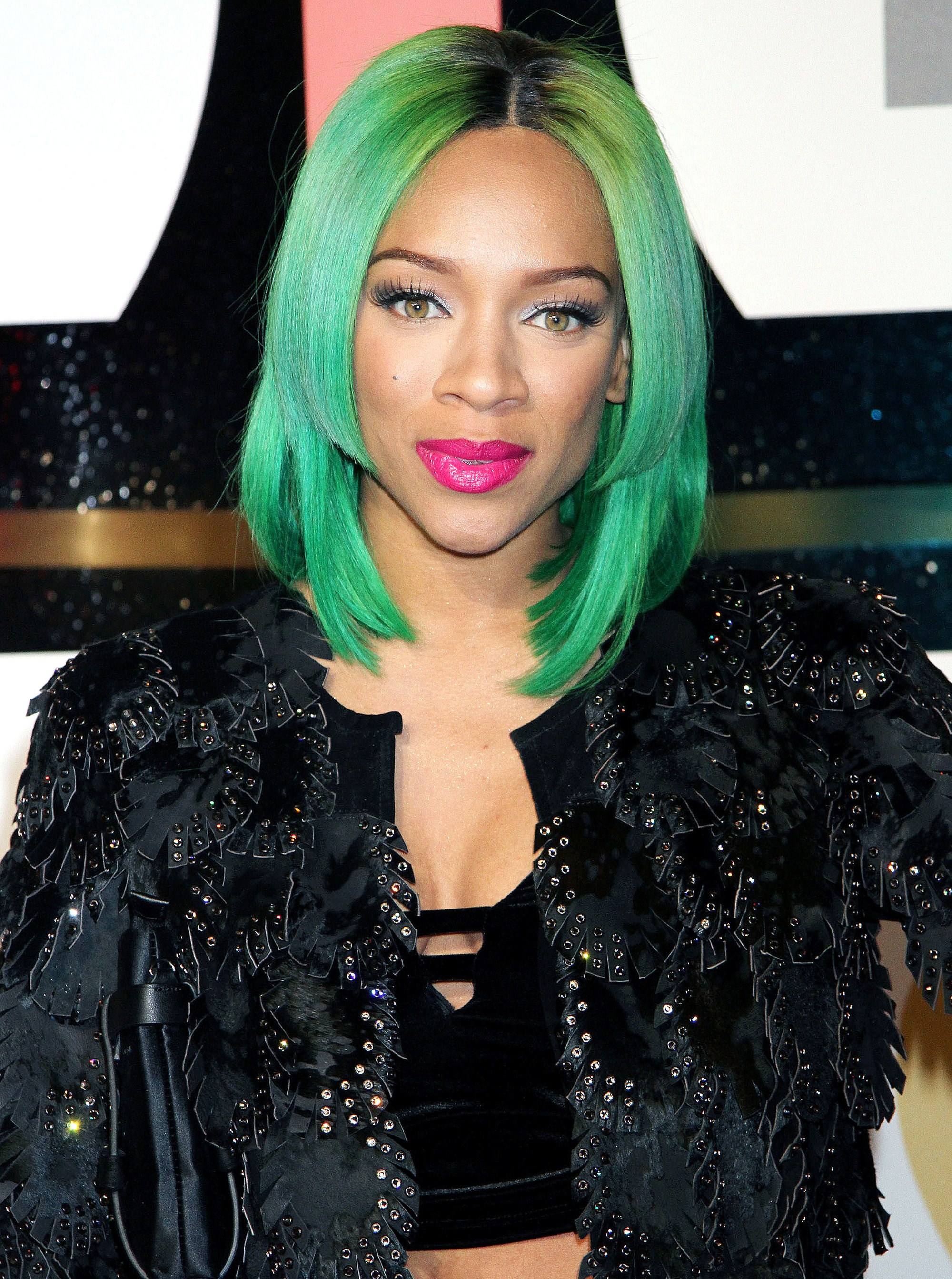 hip hop star Niatia Jessica Kirkland aka lil mama with a straight green lob hairstyle wearing a black velvet bralette with an embroidered black jacket over the top