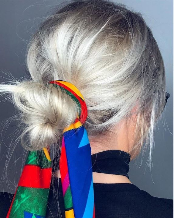 Second day hair: Woman with light silver blonde hair in low messy bun wrapped with a silk scarf.