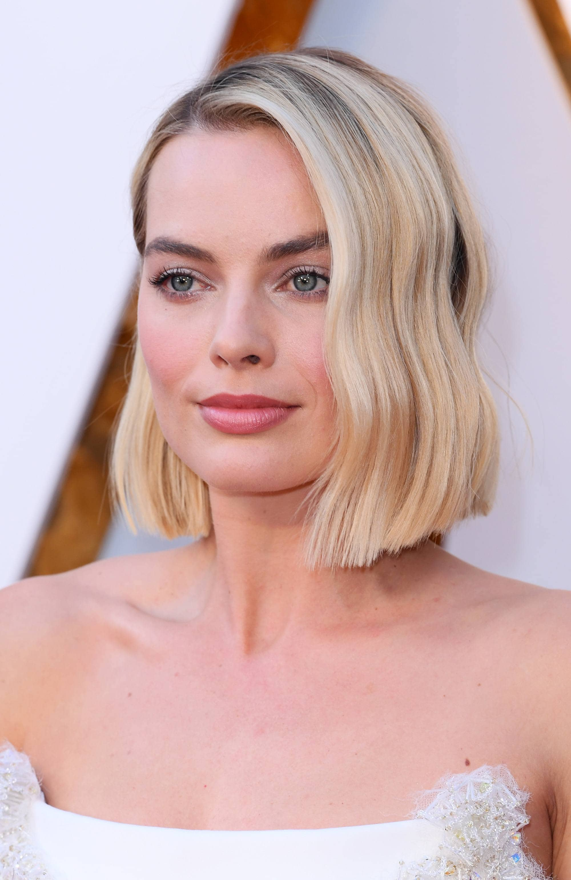margot robbie wears popular short hairstyle blunt wavy blonde bob at oscars 2018 with strapless white dress