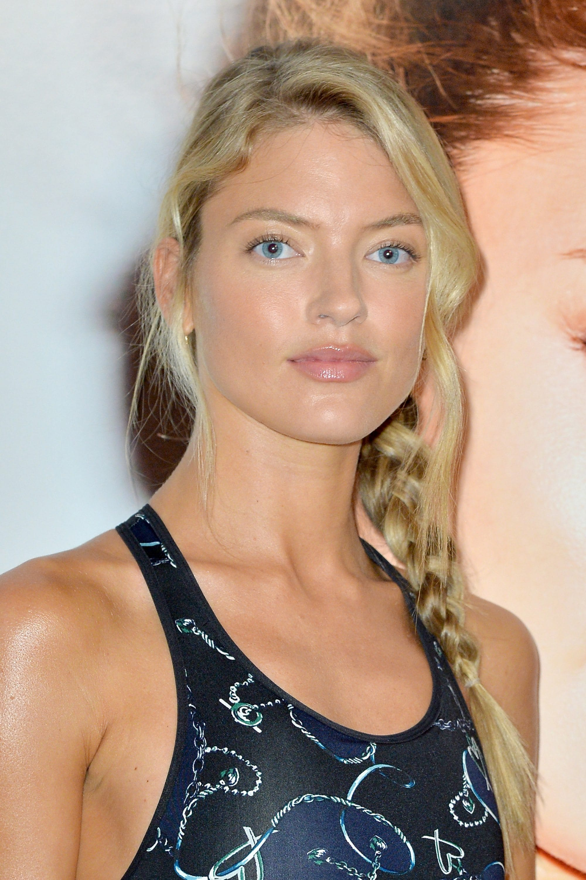 Side braid hairstyles: Martha Hunt with medium-length blonde hair in a side plait wearing a vest top.