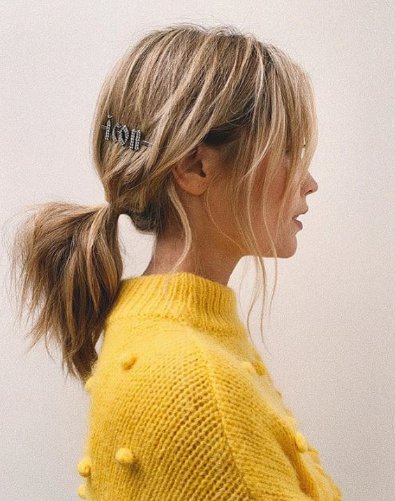 Second day hair: Laura Whitmore with blonde highlighted hair in a low ponytail with jewelled hair clip wearing a yellow jumper.