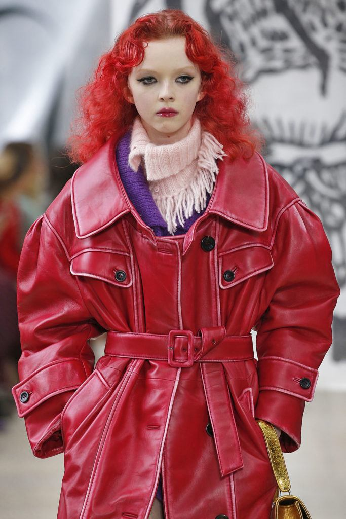 model on the miu miu aw18 runway with long curly strawberry red hair wearing bold eye makeup and a red leather trench coat