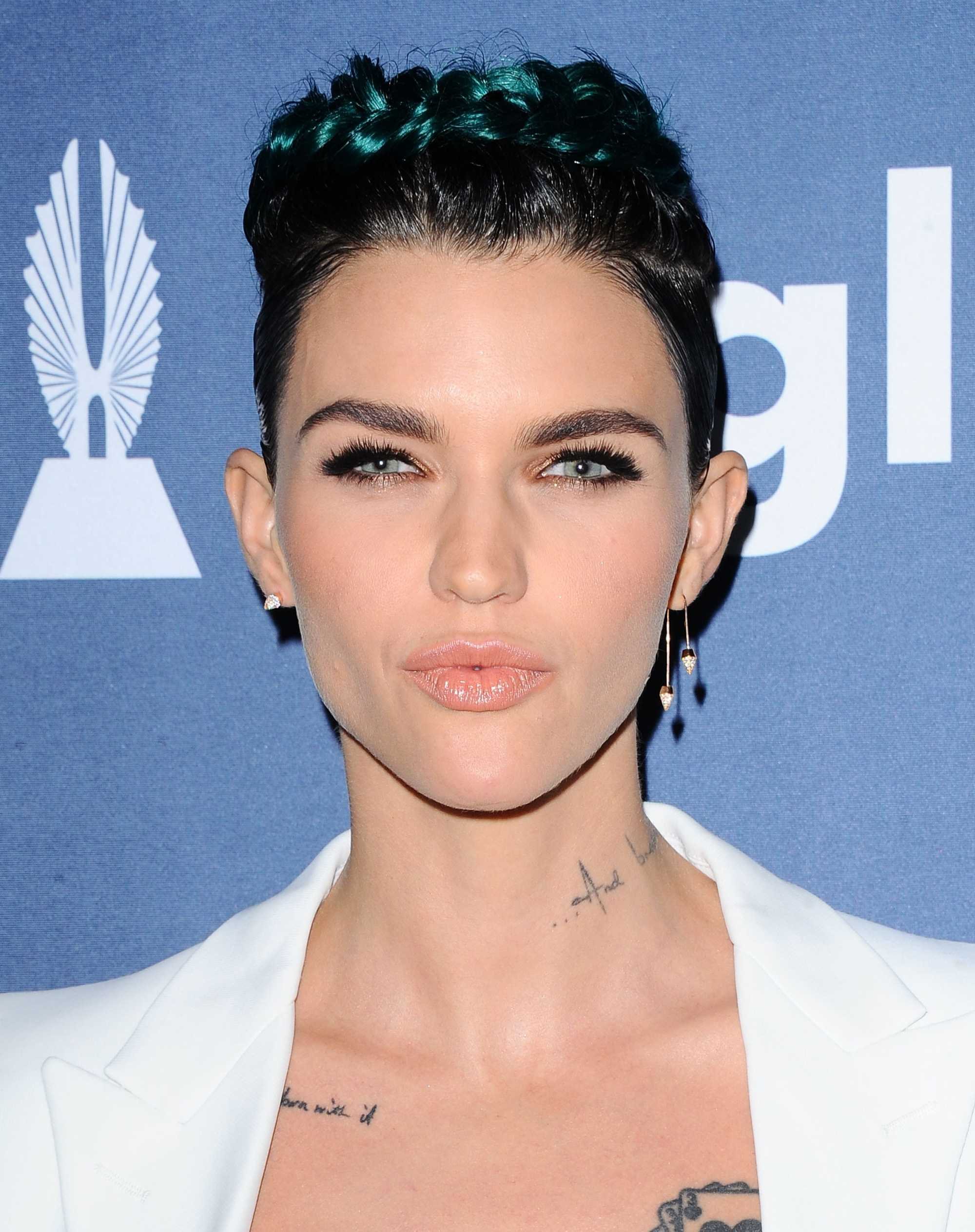 actress ruby rose with dark green pixie hair in a braided headband style wearing a white blazer jacket