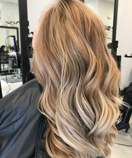 back view of a woman in the salon with long curly sandy strawberry blonde hair