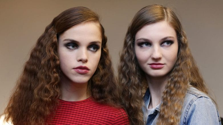 models backstage with medium length hair in side parting with smooth roots and wavy lengths wearing red jumper and denim jacket